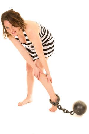 prison ball: A woman in her prison striped outfit with a ball and chain on her ankle.