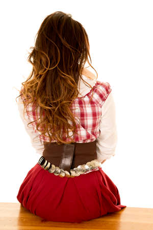 western clothing: a woman in her western clothing, sitting on a bench, with her back to the camera.