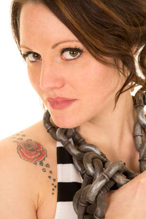 female sexy chains: a close up of a woman with a rose tattoo on her shoulder with a chain around her neck, looking.