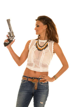 A cowgirl with her gun pointed up looking to the side.