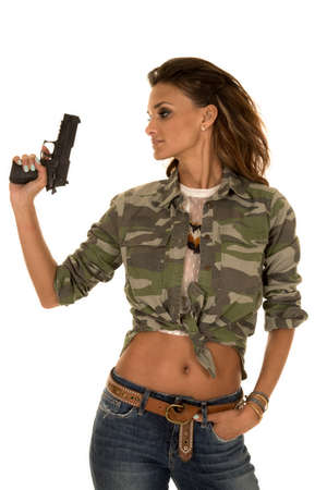 a woman holding up her pistol looking to the side. photo