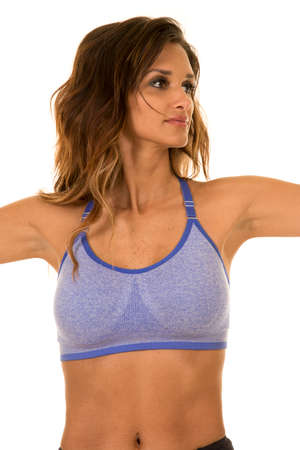 arms out: A woman in her blue sports bra with her arms out.