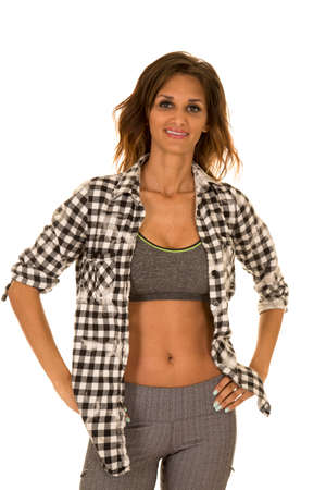 hand bra: A woman with a checkered top and sports bra with her hand on her hip. Stock Photo
