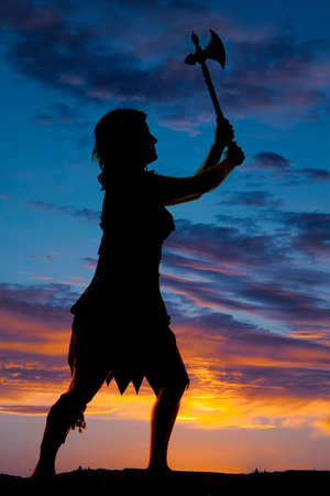 Ņhatchet: a silhouette of a cave woman with her hatchet up in the air. Stock Photo