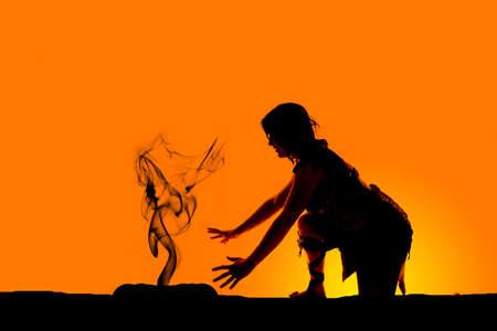 mujer rodillas: Una silueta de una mujer de la cueva de rodillas por un incendio. Foto de archivo
