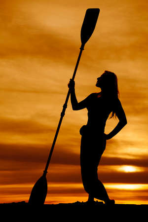 canoe paddle: A silhouette of a woman holding on to her canoe paddle in the outdoors.