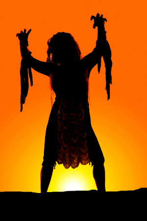 A silhouette of a woman in her Halloween costume reaching out. photo