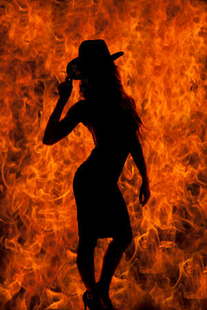 black cowgirl: A silhouette of a woman in her western hat and dress, with a fire background.