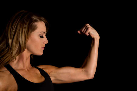 flexed: A woman looking down at her flexed muscle. Stock Photo