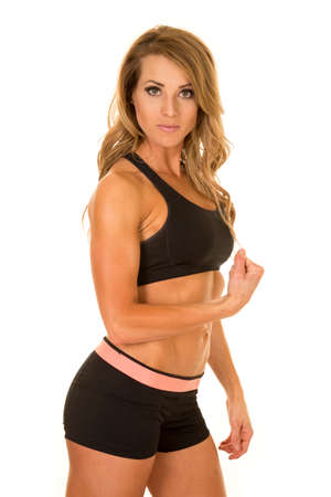 flexed: A fit woman looking with her arm flexed and posing.
