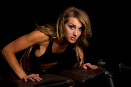push: A fit woman doing a push up on a bench. Stock Photo