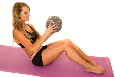 weighted: A fit woman in crunch position, working out with her weighted medicine ball.