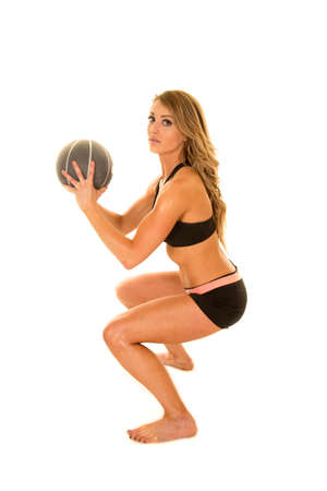 sport balls: A woman doing a squat with her fitness ball in her hands. Stock Photo