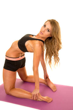 laying on back: A fit woman laying back stretching with a serious expression.