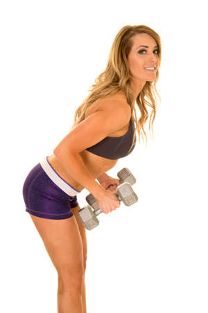 A fit woman bending down doing a row with weighs.