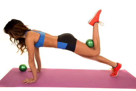 weighted: a woman in plank using a green weighted ball to work out her legs and butt.