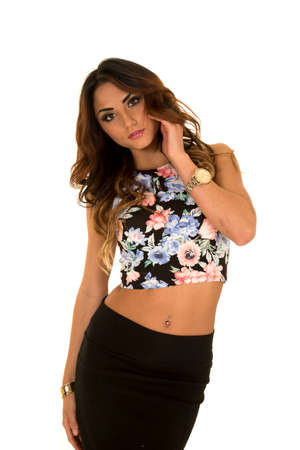 attractive gorgeous: A woman in her floral top, and skirt with her hands in her hair.