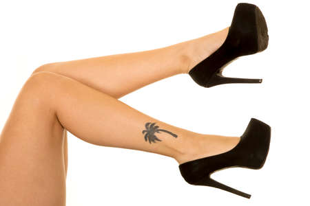 feet naked: A woman in her heel shoes with her tattoo showing.