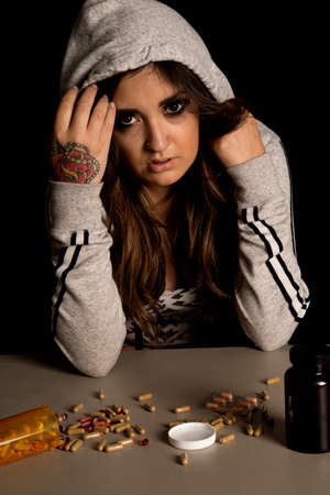 pulled over: A woman with her jacket pulled over her head, looking at the pills on the table, with a troubled expression on her face. Stock Photo