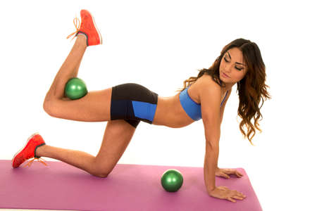 weighted: a woman using a weighted ball to workout her body.