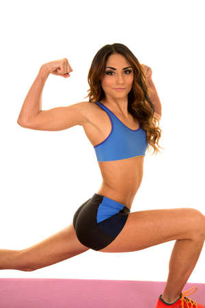 flexed: a woman in her fitness clothing lunging with her arms flexed. Stock Photo