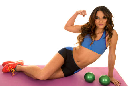 weighted: a woman sitting by her weighted green ball, with her arm flexed.