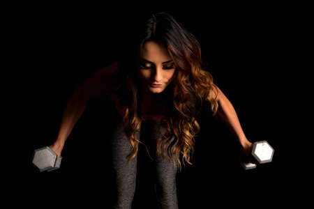 leaning forward: A woman leaning forward holding on to her weights.