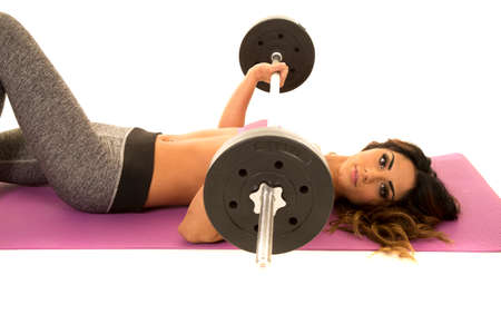 weighted: a woman laying down doing working out with a weighted bar, looking.