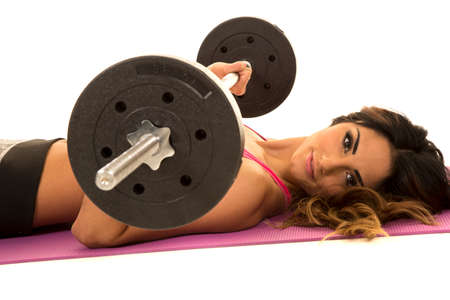 weighted: a close up of a woman laying working out with a weighted bar.