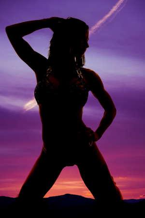 mujer arrodillada: Una silueta de una mujer arrodillada en el suelo en el aire libre.