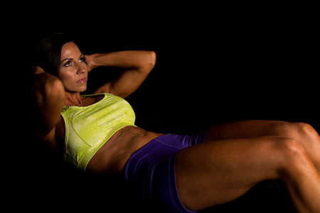 tight fit: A fit woman doing a crunch with a serious expression Stock Photo