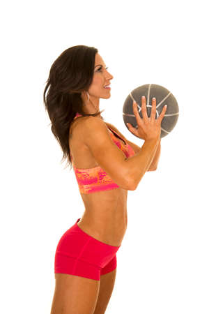 weighted: a woman in her outfit working out with a weighted medicine ball.