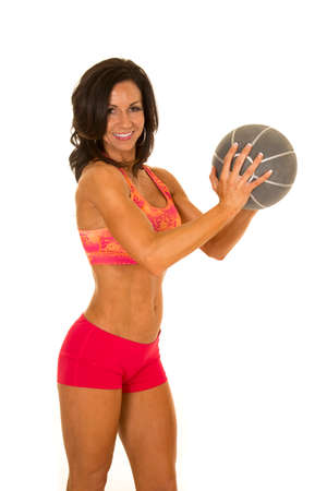 weighted: a woman in her fitness clothing, working out with a weighted medicine ball.