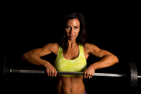 weighted: a woman working out with a weighted barbell, with a serious expression.