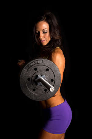 tight fit: a woman working out with weights, doing a barbell curl