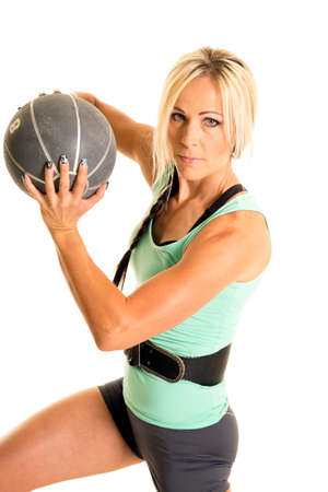 weighted: A woman with a weighted ball, twisting her body.