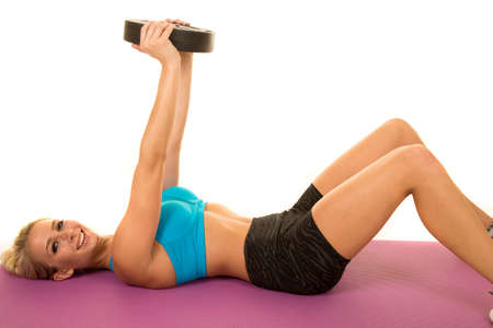 a blond woman laying down with a weight and a smile working out