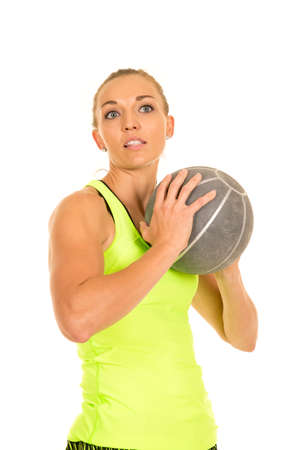 weighted: a woman holding on to a weighted medicine ball with a far away expression.
