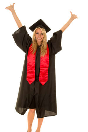 graduating: A woman with a big smile on her face with her arms raised high graduating.