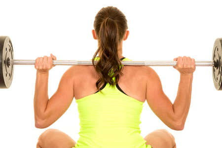 tight fit: a woman doing a squat with a weighted bar across her back. Stock Photo