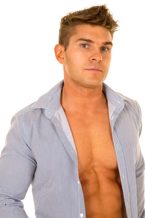 shirt unbuttoned: a man with a serious expression and his dress shirt unbuttoned showing off his muscular chest.