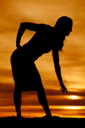 bending down: A silhouette of a woman in her fitted dress, bending down to get something.