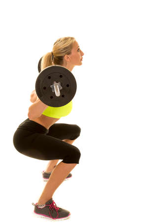 weighted: A woman doing a weighted squat with the bar on her back
