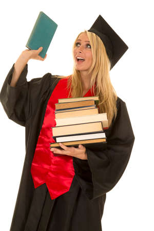 graduating: A woman who is graduating holding up a book with a smile on her face. Stock Photo