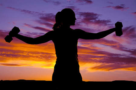 a silhouette of a woman doing lateral raises with weights. Banco de Imagens