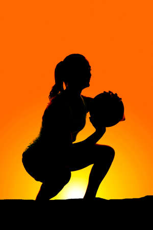 weighted: a silhouette of a woman squating in the outdoors with a weighted ball. Stock Photo