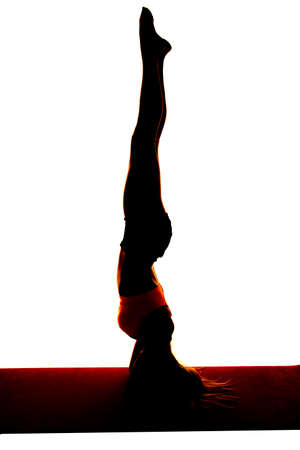 straight up: a silhouette of a woman doing a headstand with legs straight up.