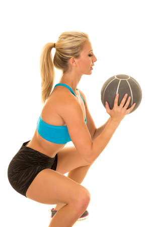 weighted: a woman doing a squat wtih a weighted ball.