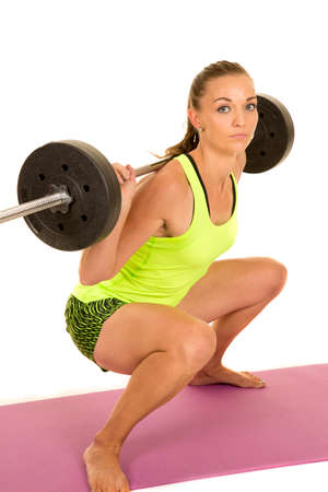 squat: A woman with a serious expression, doing a weighted squat,
