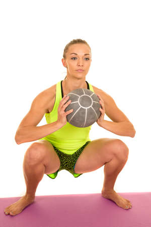 weighted: a woman doing a weighted squat with a medicine ball.
